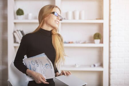Portrait of charming blonde woman with document in hands daydreaming in modern office. White shelves with various objects in the background Stock Photo