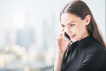 Side view portrait of happy smiling businesslady having cell phone conversation on blurry city background