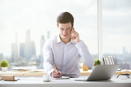 handphone: Smiling young businessman talking on mobile phone and writing something in notepad