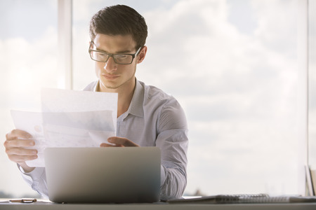 Young caucasian businessman in glasses looking carefully and business report Stok Fotoğraf