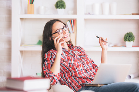 Portrait of happy young woman in glasses talking on phone and using laptop at workplace