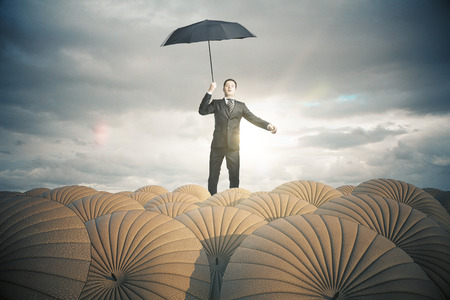 stormy sky: Young businessman in suit with brown umbrellas on stormy sky background. Business protection concept. 3D Rendering