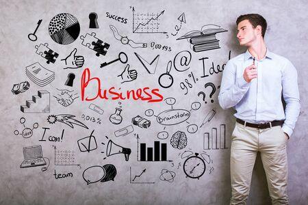 tormenta de ideas: Joven empresario de pie contra el muro de hormigón de textura con el bosquejo de negocios. el concepto de éxito
