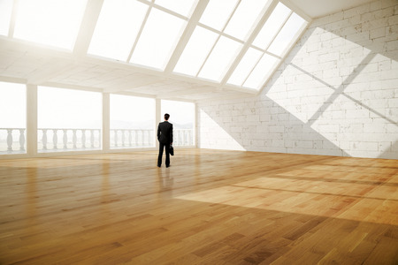balcony: Businessman with briefcase standing in creative empty interior with balcony, wooden floor, white brick walls and daylight. 3D Rendering Stock Photo