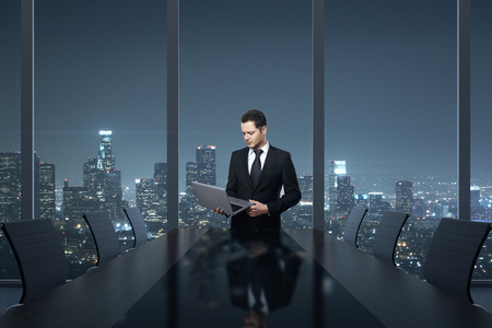 executive: Handsome young businessman using laptop computer in conference room interior with table, chairs and night city view. 3D Rendering