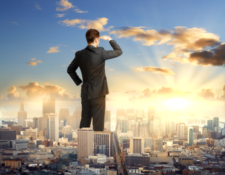 Back view of young businessman in suit standing in abstract tiny city and looking into the distance. Research concept