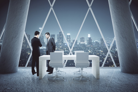 conference table: Two thoughtful businessmen standing in conference room interior with small table, concrete columns and night city view. 3D Rendering