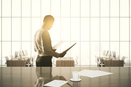examining: Side view of businessman examining contract on modern office with workplace, coffee cup, other items and windows with sunlight. 3D Rendering