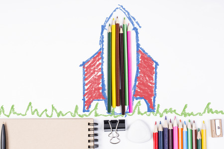Abstract rocket ship and grass sketch around colorful pencils on white desktop with supplies. Education concept Stock Photo