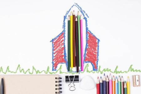 lapiz: cohete abstracto y boceto hierba alrededor de lápices de colores sobre el escritorio blanco con suministros. concepto de la educación