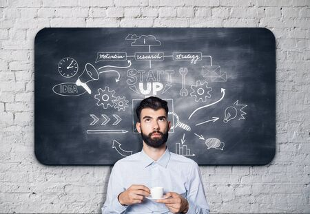 realization: Thoughtful bearded businessman with coffee cup in hands standing against chalkboard with business sketch. Startup concept Stock Photo