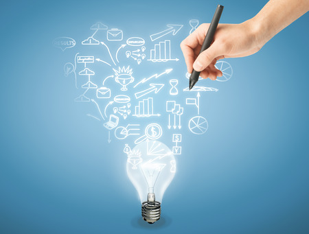 man's: Mans hand drawing business icons above light bulb on light blue background. Business idea concept