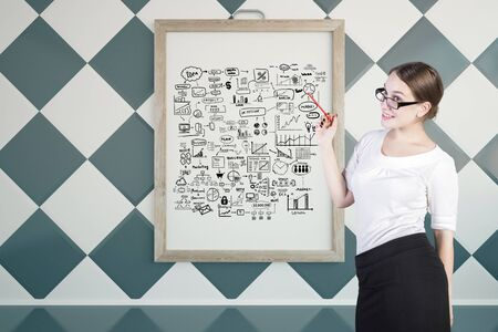 chessboard: Young businesswoman giving presentation on business with sketch in picture frame. Chessboard wall background. Success concept