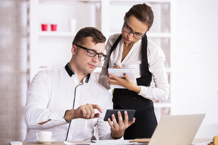 Two caucasian business people in office working on project together. Businessman and woman using smartphone and doing paperwork