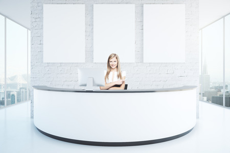 Cheerful businesswoman at reception desk with three blank posters in interior with white brick wall, shiny floor and panoramic windows with city view. Mock up, 3D Rendering