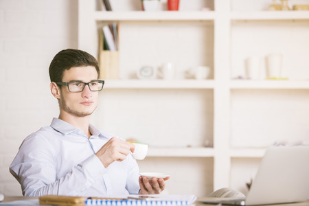 clean office: Portrait of  attractive young businessman in glasses drinking coffee in bright clean office