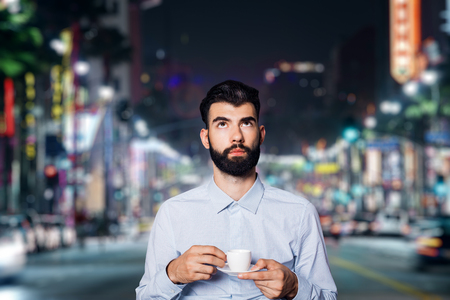 Portrait of young man with coffee cup on blurry night city background