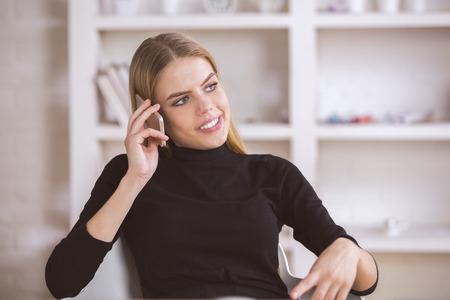 beautiful background: Portrait of happy beautiful woman talking on phone in modern office