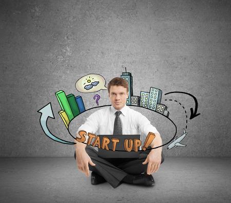hombre de negocios joven en la sala de hormigón sentado en el piso con el ordenador portátil y el croquis de inicio abstracto. Nuevo concepto de negocio