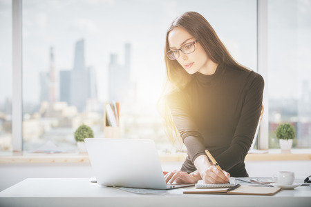 learning online: Portrait of beautiful young businesswoman working on project in bright office with panoramic city view and sunlight