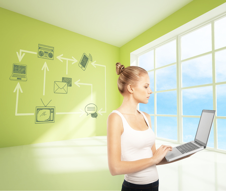 schemes: Side view of attractive caucasian woman using laptop in green interior with technology network on green wall. Window with sky view background. Communication concept Stock Photo