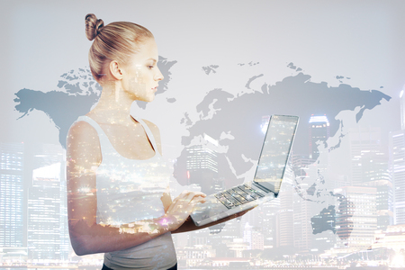 Attractive young female using laptop on city background with abstract map. Double exposure