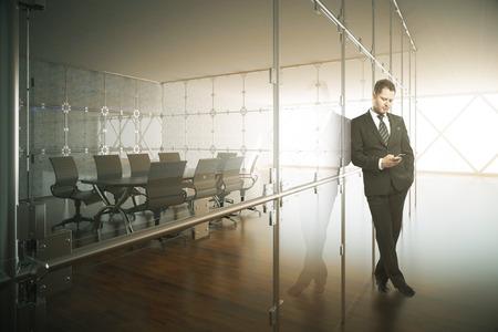 Joven empresario en traje apoyado en la pared de cristal y el uso de teléfonos inteligentes en el moderno interior de la sala de conferencias con suelo de madera y la luz del día. Representación 3D