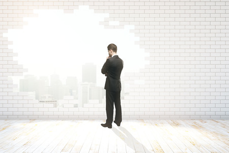 Thoughtful businessman looking out of hole with New York city view in white brick wall. 3D Rendering Stock Photo