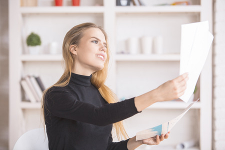 niña pensando: Portrait of attractive smiling businesswoman dealing with paperwork in modern bright office with various items on shelves Foto de archivo