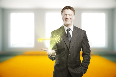 businessman in office: Handsome smiling businessman in suit holding shining golden ornate key on blurry interior background