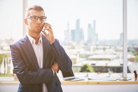 hablando por telefono: Retrato de hombre de negocios joven serio en juego que habla en el teléfono en la oficina moderna con diferentes puntos comprendidos en alféizar de la ventana y de la ciudad
