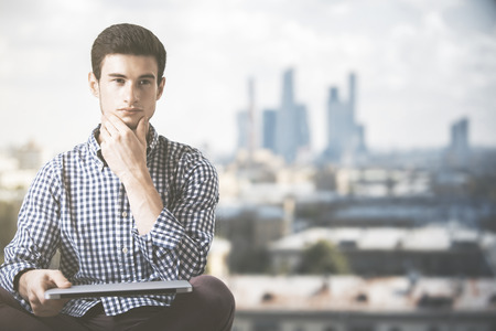 Portrait of handsome thoughtful young man in casual shirt holding closed laptop on blurry city background with copy space