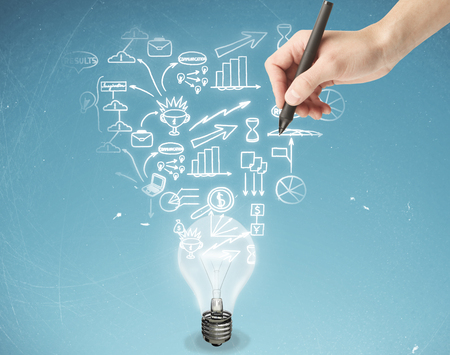 business in hand: Male hand drawing business icons above light bulb on aged blue background. Business idea concept