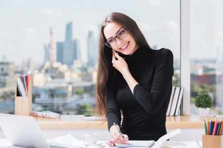 koncentrovaný: Portrét usmívající se mladé evropské businesslady v kanceláři, mluvit o mobil, pracovat na projektu a dělat papírování. Rozmazaný pohled na město v pozadí