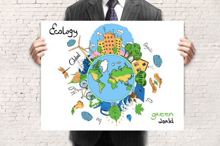 brick earth: Businessman in suit holding creative sketching of globe with natural healthy lifestyle icons on white brick wall background. Eco concept