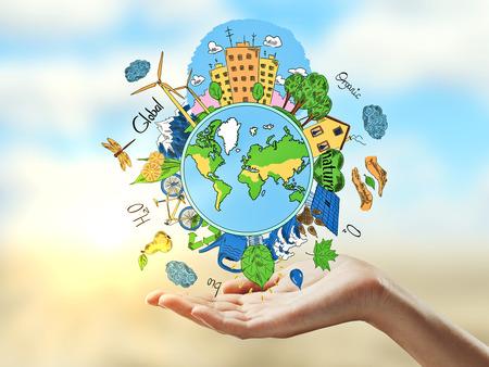 mundo manos: Manos femeninas que sostienen dibujo creativo del mundo con iconos de estilo de vida saludables naturales en el fondo borroso brillante. Concepto verde del mundo