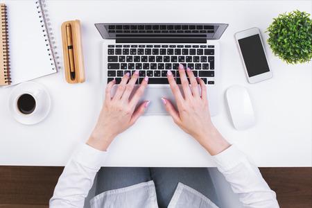 実業家の手のラップトップを使って入力の平面図は、空白のスマート フォン、コーヒー カップ、装飾的な植物の供給とホワイト オフィス デスクト
