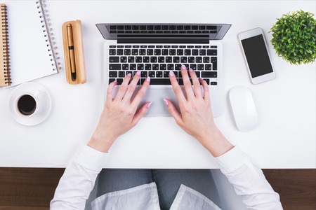 Top view of businesswomans hands typing on laptop keypad placed on white office desktop with blank smartphone, coffee cup, decorative plant and supplies. Mock up