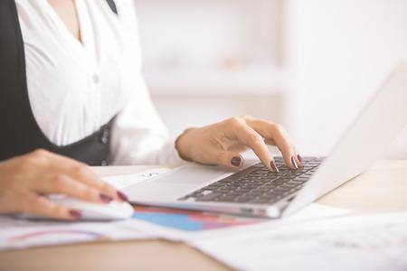 typing: Vista lateral de las manos de la empresaria escribiendo en el teclado del ordenador portátil colocado en el escritorio con los informes de negocio y documentos Foto de archivo
