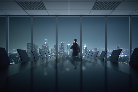 night suit: Young businessman talking on phone in conference room interior with table, chairs and night city view. 3D Rendering Stock Photo