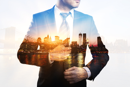 Creative image of young businessman in suit and tie on city background with sunlight. Double exposure