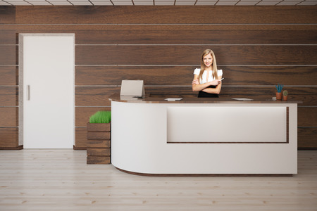 clean office: Smiling female secretary standing at reception desk in interior with white door, wooden floor and walls. 3D Rendering Stock Photo