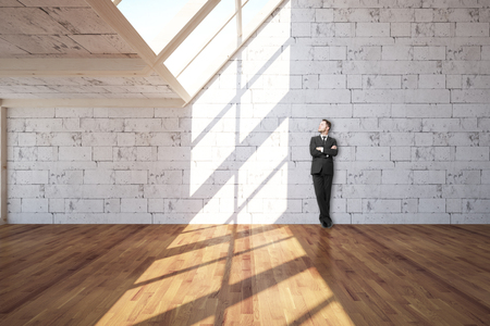 folded arms: Young businessman with folded arms leaning on white brick wall in interior with wooden floor and daylight. 3D Rendering