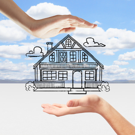 Hands holding creative house sketch on beautiful landscape background. Real estate concept