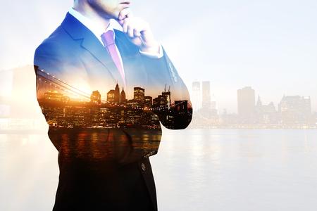 Immagine creativa della persona di affari premurosa in vestito e legame sul fondo della città con luce solare. Doppia esposizione