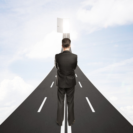 open road: Young businessman standing on road leading to abstract open door with possibilites on sky background. Success concept