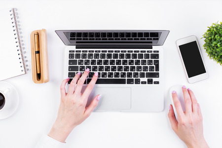 Top view of girl's hands typing on laptop keypad placed on white office desktop with blank smartphone, coffee cup, decorative plant and supplies. Mock up Stockfoto
