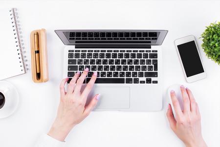 Top Blick auf Mädchen Hände tippen auf Laptop-Tastatur platziert auf weißem Büro-Desktop mit leeren Smartphone, Kaffeetasse, dekorative Anlage und Zubehör. Attrappe, Lehrmodell, Simulation Standard-Bild - 63392096