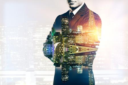 Jonge man in pak en met gevouwen armen op abstracte verlichte nacht stad achtergrond. Dubbele belichting