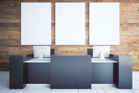 Modern black reception desk with two computer monitors and blank billboard in room with wooden wall and tile floor. Mock up, 3D Rendering Stock Photo